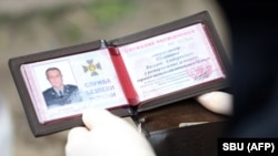 This handout picture taken and released on April 14 by the Security Service of Ukraine shows an officer reading a document of Valeriy Shaytanov during his arrest.
