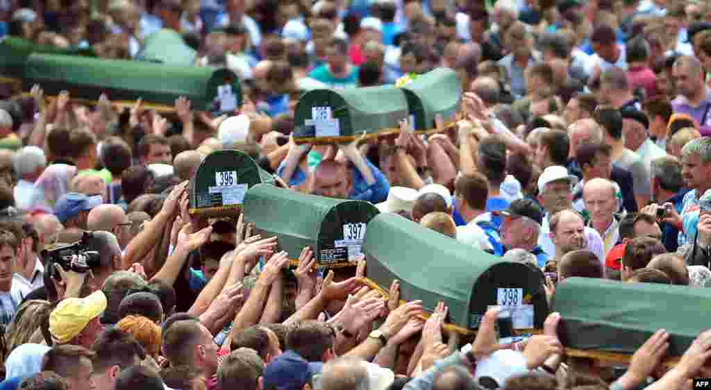 Bosnian Muslims carry caskets containing the bodies of people killed in the 1995 Srebrenica massacre as they prepare for a mass burial during a memorial ceremony in the village of Potocari on July 11, the 18th anniversary of the killings. (AFP/Elvis Barukcic)