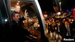 Turkish Prime Minister Recep Tayyip Erdogan (2nd left) waves to supporters after arriving at Istanbul's Ataturk Airport early on June 7.