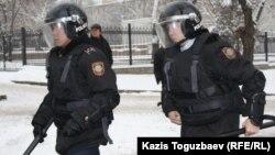 Тәуелсіздік монументі түбіндегі жиынды бақылауға бара жатқан полицейлер. Алматы, 17 желтоқсан 2011 жыл. (Көрнекі сурет)