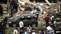 People gather at the site of a bomb that targeted the convoy of Egyptian Interior Minister Muhammad Ibrahim in Cairo.