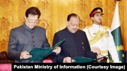 Imran Khan (left) takes the oath of office as Pakistani prime minister with President Mamnoon Hussain in attendance on August 18.
