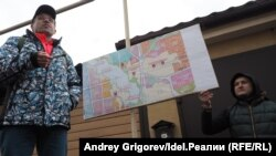 """Ильхам Шагараев (слева) объясняет жителям поселка на сходе, чем грозят """"дополнения"""" в Генплан."""
