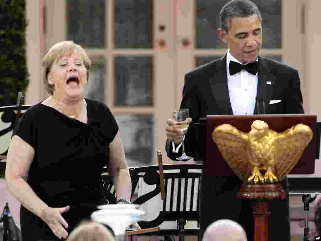 German Chancellor Angela Merkel reacts as U.S. President Barack Obama raises a toast in her honor -- after realizing that he had forgotten to do so -- at a state dinner at the White House in Washington.Photo by Pablo Martinez Monsivais for AP