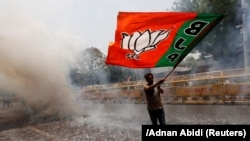 A BJP supporter waves a party flag as he celebrates after learning the initial election results in New Delhi, on May 23.