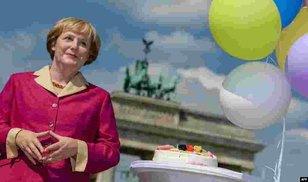 A wax likeness of German Chancellor Angela Merkel pictured in front of the Brandenburg Gate in Berlin on the occassion of her 60th birthday.