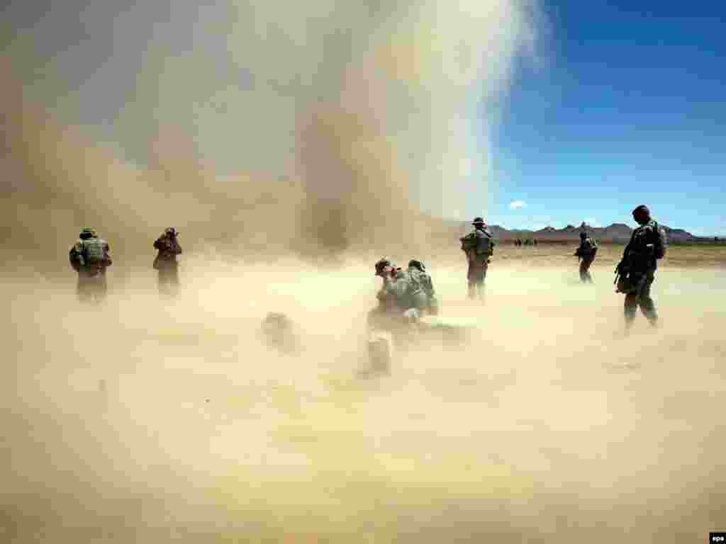 U.S. soldiers struggle with a sandstorm ahead of a training session with servicemen of the Afghan National Army near Herat. Photo by Tiago Petinga for epa