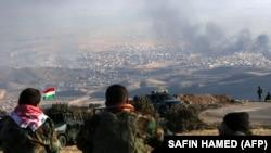 Luftëtarët kurdë duke e shikuar tymin në Sinxhar gjatë një operacioni të forcave kurde të mbështetura nga sulmet ajrore të SHBA-ve