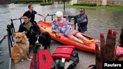Спасатели помогают жителям города Дикинсон и их домашним животным, пострадавшим в результате наводнения, вызванного ураганом «Харви», штат Техас, 27 августа 2017 года