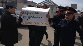 Ресей елшілігі алдында наразылық танытқан Астана тұрғыны Мұратбек Арғынбековті (ортада) полиция әкетіп бара жатыр. 14 сәуір 2014 жыл.