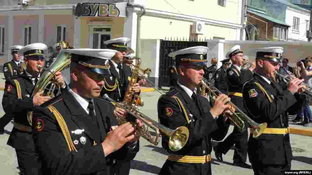 Праздничное настроение участникам демонстрации создает духовой оркестр. Музыканты непрерывно играют марши.