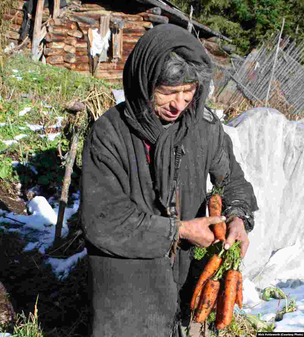 Dressed in tattered sackcloth, Agafia Lykova holds carrots, one of the root vegetables that she grows by her home in southern Siberia.