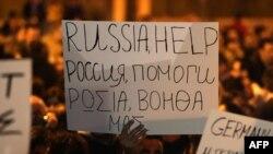 Кіпріоти шукають допомоги, але досі не мають політичної волі до рішучих заходів. Протестувальник під стінами парламентк тримає плакат «Росіє, допоможи», Нікосія, 21 березня 2013 року