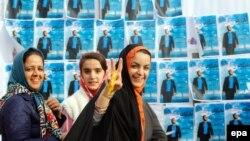 Женщины рядом с плакатами с предвыборной агитацией. Кередж, 22 февраля 2016 года.