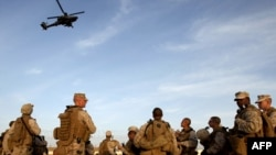 U.S. Marines watch a U.S. helicopter gunship after landing to join an American contingent in the southern Helmand Province in February.