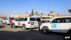 UN and International Committee of the Red Cross vehicles wait to pass through the Wafideen checkpoint on the outskirts of the capital, Damascus, on March 9.