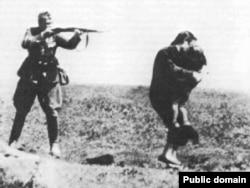 Фашистский солдат расстреливает женщину с ребенком в Бабьем Яру, на месте массового убийства вблизи Киева. Иллюстративное фото.