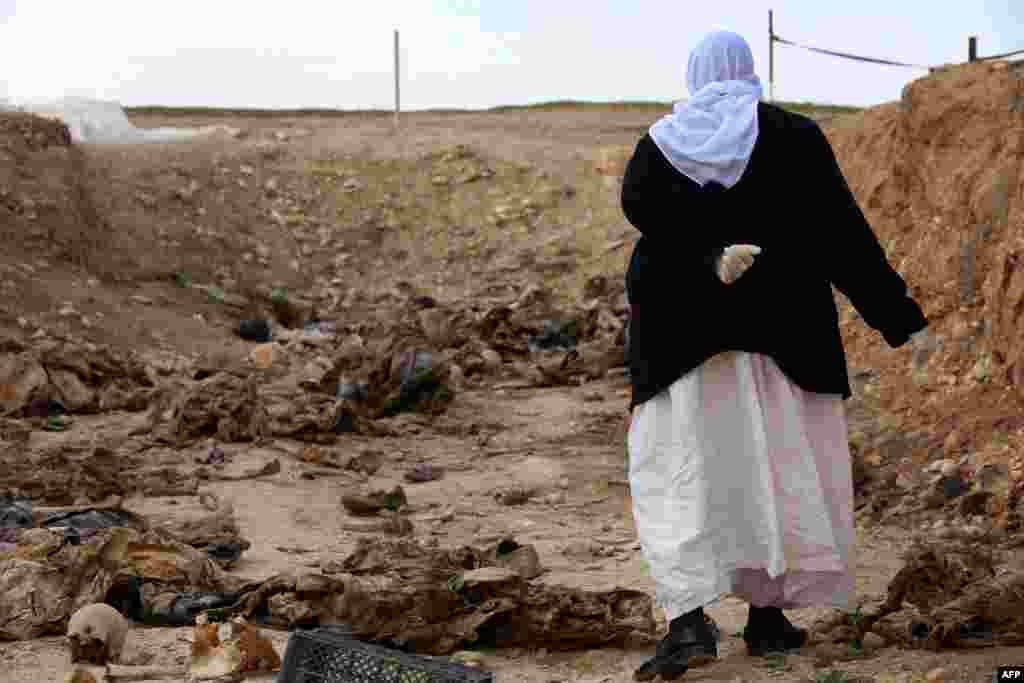 A Yazidi woman searches for clues as to the whereabouts of missing relatives among the remains at a mass grave in Iraq of victims of Islamic State (IS) gunmen. (AFP/Safin Hamed)