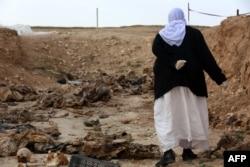 Пожилая езидка ищет останки своих родственников, убитых исламистами, в обнаруженной на севере Ирака общей могиле. Февраль 2015 года