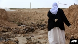 A Yazidi woman searches for clues in February 2015 as to the whereabouts of missing relatives among remains at a mass grave of victims of Islamic State (IS) militants in Iraq's Sinjar region.