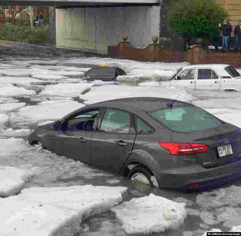 Cars drift among clumps of ice on the streets of Gyumri, Armenia. This is the aftermath of a combined rain and hailstorm that struck Armenia's second city on July 13.