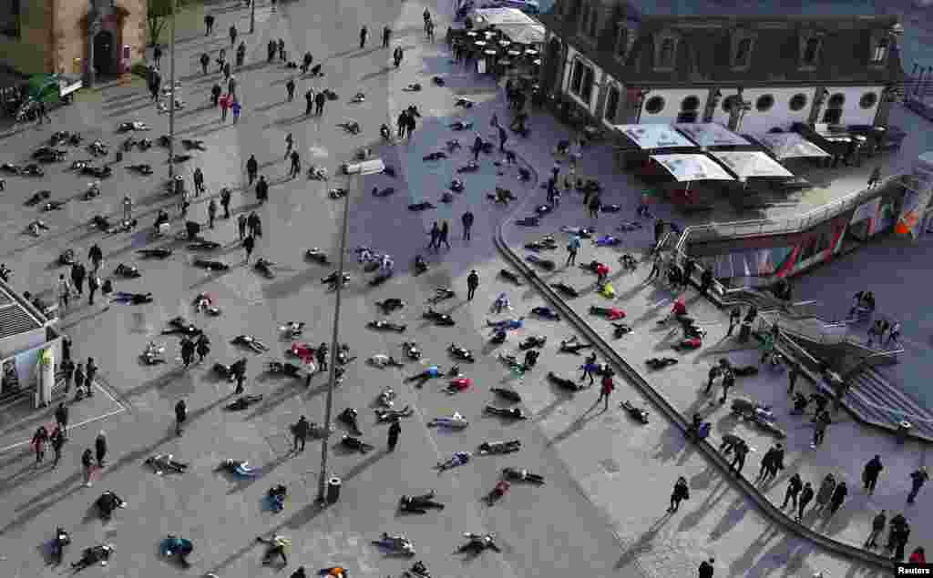 People lie down in a pedestrian zone of Frankfurt on March 24 as part of an art project in remembrance of the 528 victims of the Katzbach Nazi concentration camp. (Reuters/Kai Pfaffenbach)