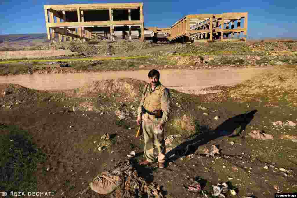 یکی از پیمرگه های کرد در نزدیکی یکی از گورهای دستجمعی داعش
