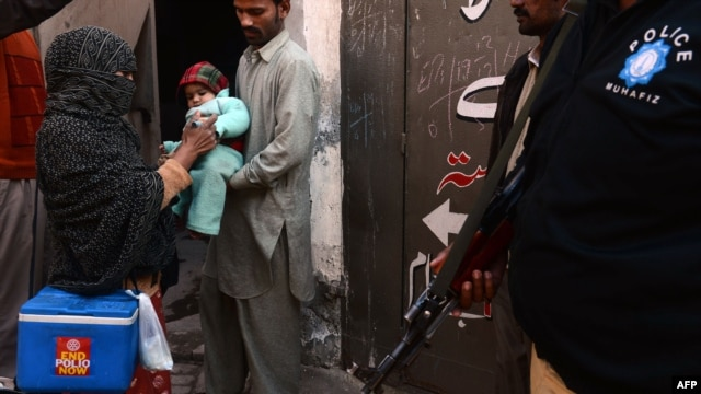 A Pakistani policeman stands guard as a polio-vaccination worker marks a child after immunization with antipolio drops in Lahore on December 21.