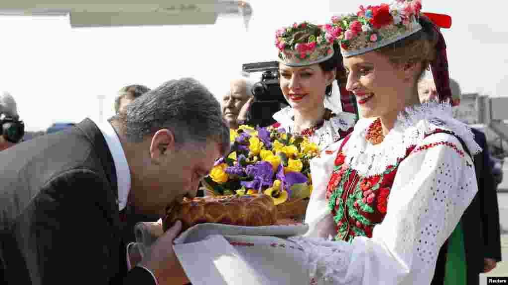 Украина президенті Петр Порошенко өзін әуежайда қарсы алғанда ежелгі дәстүр бойынша ұсынылған нан-тұздан дәм татып тұр.Минск, 26 тамыз 2014 жыл.