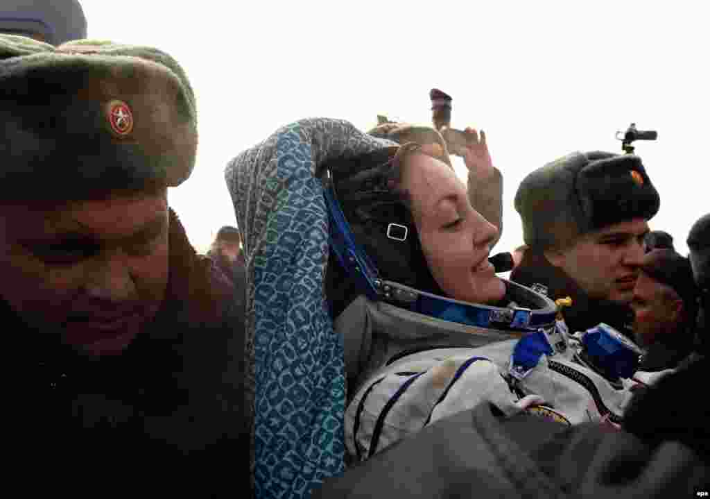 Russia's space agency ground personnel help cosmonaut Yelena Serova after landing.
