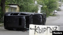 "A concrete block with a sign saying ""Kyrgyz Zone"" stands in a street in the city of Osh on June 13."