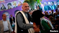 Afghan presidential candidate Ashraf Ghani Ahmadzai greets a girl at a campaign appearance in Jozjan Province on June 2.