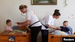 Няни ухаживают за детьми в приюте для инвалидов