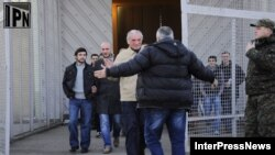 Inmates recently classified as political prisoners leave a Georgian prison on January 13.