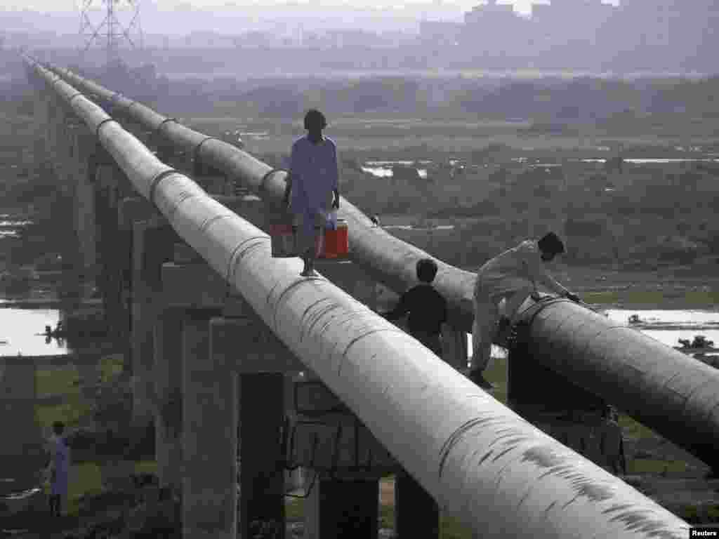 A man walks on a water pipeline as he carries buckets of water in Karachi, Pakistan.Photo by Athar Hussain for Reuters