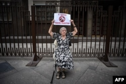 "Lyudmila Alekseyeva holds a poster reading ""I oppose sadists' law"" as she pickets against Russia's NGO law in front of the State Duma in Moscow in May 2015."