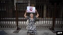 """A Moszkvai Helsinki Csoport elnöke és a Kreml emberi jogi tanácsának tagja, Ljudmila Alekszejeva posztert tart fel a Duma épülete előtt 2015. május 29-én azzal a felirattal, hogy """"Ellenzem a szadisták törvényeit""""."""