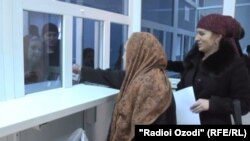 Родственники таджикских мигрантов, работающих в России, получают деньги через банк.