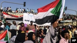 SUDAN -- Sudanese demonstrators march with national flags as they gather during a rally demanding a civilian body to lead the transition to democracy, outside the army headquarters in the Sudanese capital Khartoum on Saturday, April 13, 2019.