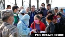 Коронавирус инфекциясына байланысты карантин кезінде билік өкілдері Алматы қаласынан шығып бара жатқан азаматтардың аты-жөнін, туған жылы мен телефон нөмірін жазып алып жатыр. 19 наурыз 2020 жыл. Көрнекі сурет.