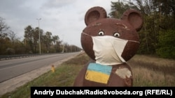 Олімпійський Мішка (символ московської Олімпіади 1980 року, частину змагань якої приймав Київ) у медичній масці на в'їзді до української столиці, весна 2020 року