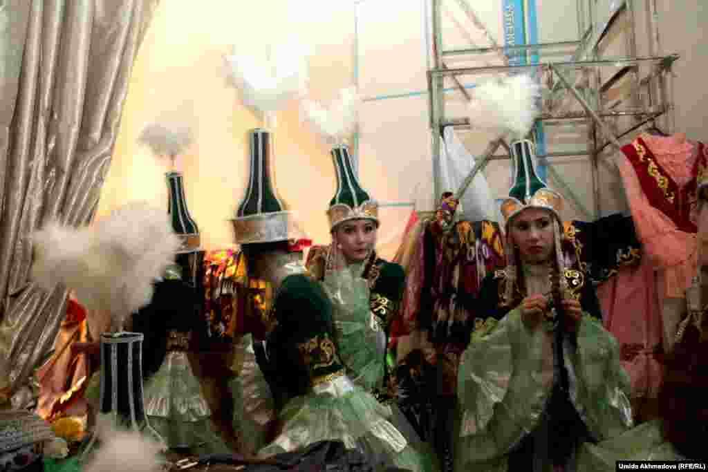 Девушки в казахских национальных костюмах готовятся к выходу на сцену.