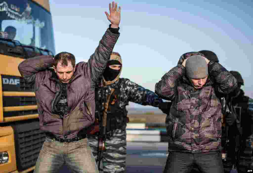 Men hold their hands on their heads as they are searched by pro-Russian servicemen at the Chongar checkpoint at the entrance to Ukraine's Crimea, which is currently occupied by Russian forces. (AFP/Alisa Borovikova)