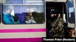 Jedan od ratnika iz Srbije na ukrajinskom ratištu, Bratislav Živković, član četničke paravojne grupe, proverava putnike na cesti između Simferopolja i Sevastopolja 2014. godine