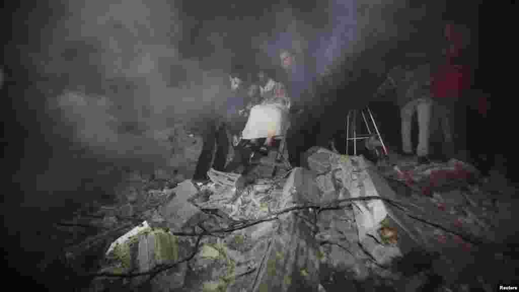 Палестинці виносять старшу жінку з руїн дому після ізраїльського удару в місті Газа, фото 14 листопада 2012 року