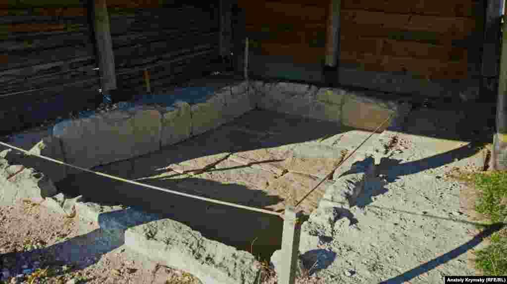 Ритуальный бассейн под современной деревянной крышей.