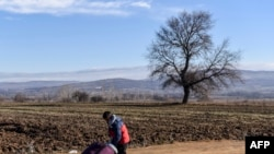 A boy pushes a suitcase as he walks with other migrants and refugees after crossing the Macedonian border into Serbia near the village of Miratovac. (AFP/Armend Nimani)
