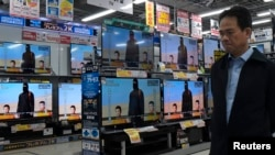 A man walks past televisions sets displaying a news program about an Islamic State video purporting to show two Japanese captives at an electronics store in Tokyo on January 20.