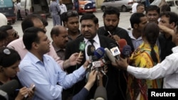 Prosecutor Chaudhry Zulfikar (center) talking to journalists outside a court in Rawalpindi on April 26.