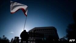 Мужчина с крымским флагом сидит на лавке недалеко от крымского парламента. Симферополь, 18 марта 2014 года.